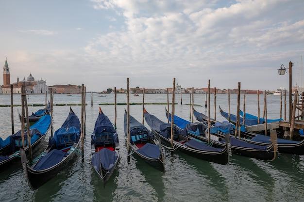 Vista panorâmica da laguna veneta da cidade de veneza com gôndolas e distância da ilha de san giorgio maggiore. paisagem de manhã de verão e céu azul dramático
