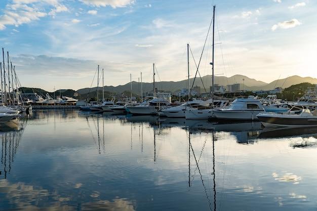 Vista panorâmica da luxuosa marina com muitos veleiros no cais durante o pôr do sol.