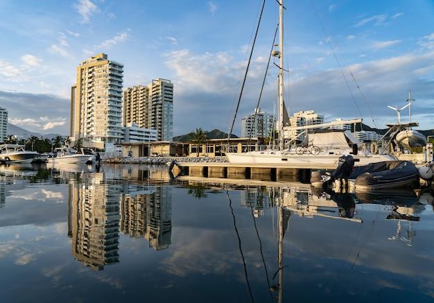 Vista panorâmica da marina de luxo com o veleiro no cais durante o pôr do sol.