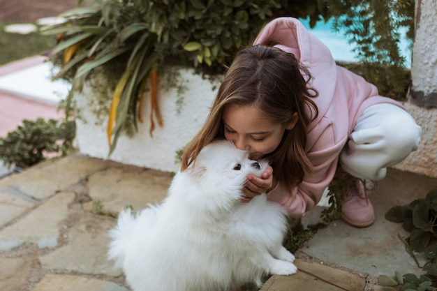 Vista panorâmica da menina beijando o cachorro