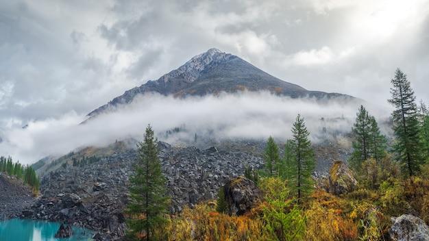 Vista panorâmica da montanha de outono, uma estreita faixa de névoa sobre as encostas da montanha ao longe, nuvens brancas enchendo o desfiladeiro da montanha. um lago de montanha azul claro e uma floresta de outono brilhante.