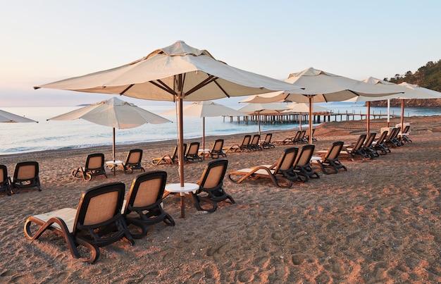 Vista panorâmica da praia de areia na praia com espreguiçadeiras e guarda-sóis aberta contra o mar e as montanhas. hotel de luxo amara dolce vita. recorrer. tekirova-kemer. peru