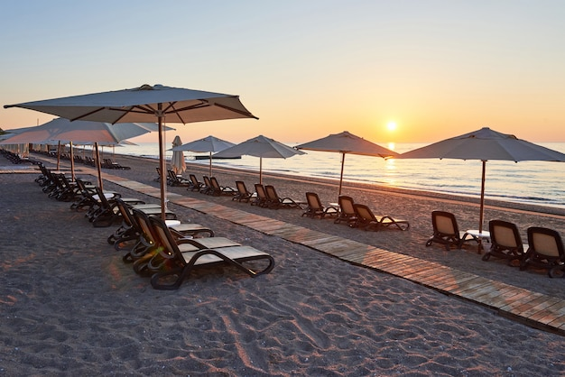 Vista panorâmica da praia de areia na praia com espreguiçadeiras e guarda-sóis aberta contra o mar e as montanhas. hotel. recorrer. tekirova-kemer. peru
