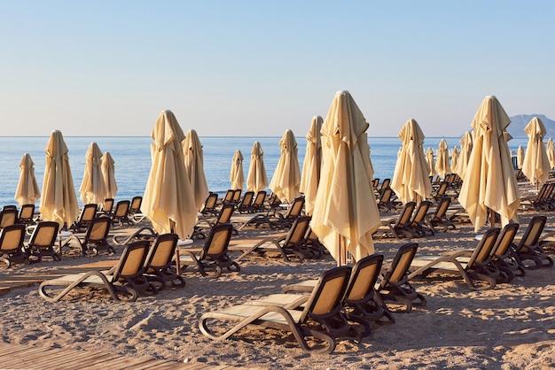 Vista panorâmica da praia privada com espreguiçadeiras e parasokamy o mar e as montanhas. recorrer.