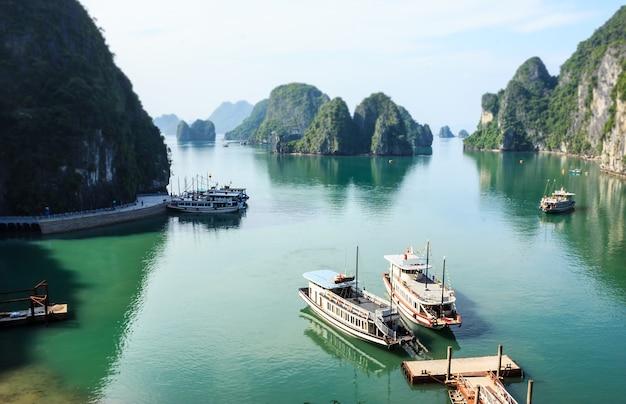 Vista panorâmica das ilhas de ha long bay, barco turístico e mar de bo hon island