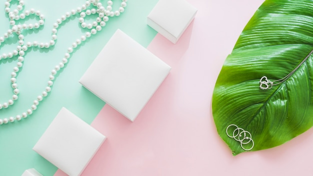 Vista panorâmica de caixas brancas com jóias femininas em fundo de papel
