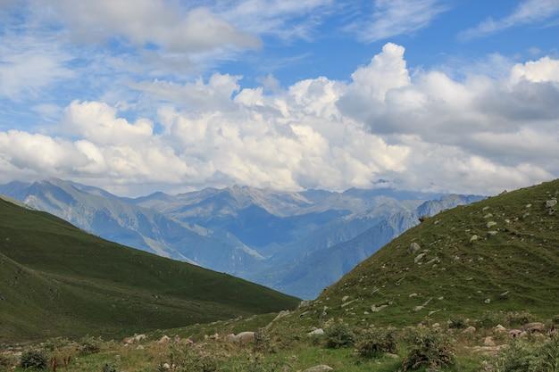 Vista panorâmica de cenas de montanhas no parque nacional de dombay, cáucaso, rússia, europa. céu azul dramático e paisagem ensolarada de verão
