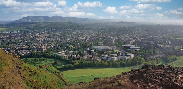 Vista panorâmica de edimburgo de uma colina. vegetação, colinas, edifícios, mar ao longe