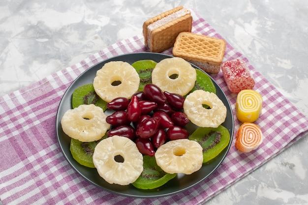 Vista panorâmica de frutas secas abacaxi anéis waffles de dogwoods e fatias de kiwi na mesa branca