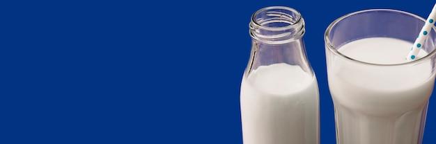 Vista panorâmica de leite no copo e garrafa em fundo azul