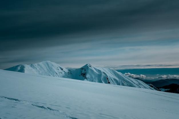Vista panorâmica de montanhas cobertas de neve tocando as nuvens