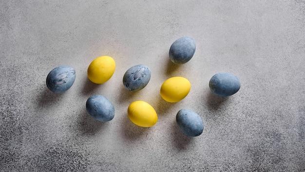 Vista panorâmica de ovos de páscoa caseiros coloridos em mármore amarelo e cinza na vista superior da mesa de madeira