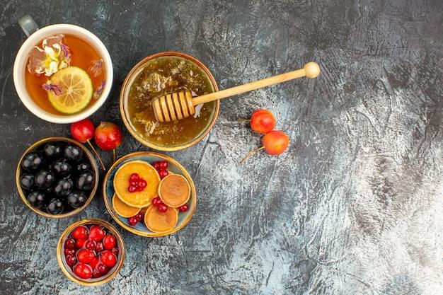 Vista panorâmica de panquecas clássicas servidas com mel e uma xícara de chá