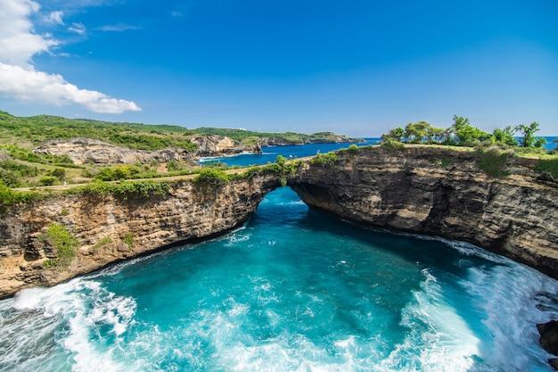 Vista panorâmica de praia quebrada em nusa penida, bali, indonésia. céu azul, água turquesa.