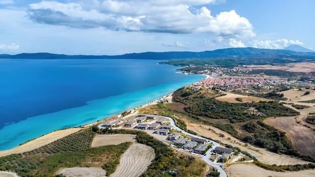 Vista panorâmica de stratonion do drone, vários edifícios na costa do mar egeu, colinas cobertas por uma vegetação exuberante, grécia