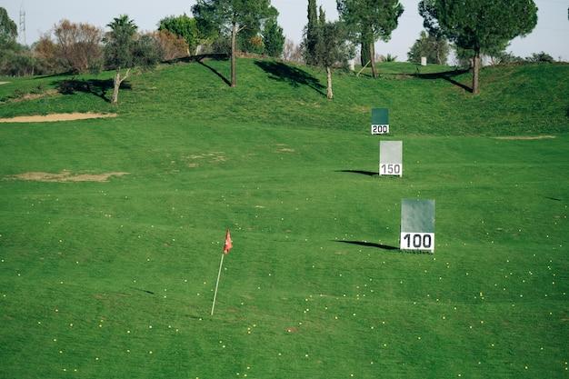 Vista panorâmica de um campo de prática de golfe com sinais de metros alcançados.