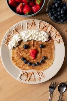 Vista panorâmica de um crepe engraçado decorado com chantilly e frutas vermelhas no prato, café da manhã no dia dos pais