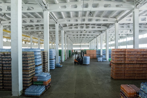 Vista panorâmica de um grande armazém com bebidas em garrafas plásticas com máquinas de carregamento