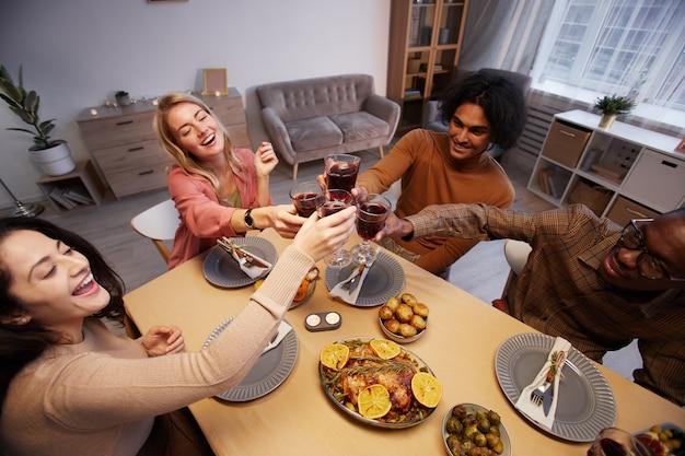 Vista panorâmica de um grupo multiétnico de jovens alegres brindando enquanto desfrutam de um jantar com amigos e familiares