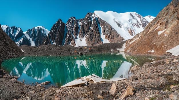 Vista panorâmica de um lago de montanha azul em altai com tendas na costa. um belo lago turquesa. lago transparente incomum no outono.
