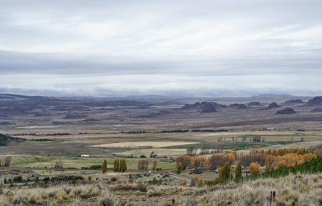 Vista panorâmica de um vale distante com montanhas e grandes prados para a agricultura