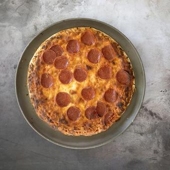 Vista panorâmica de uma deliciosa pizza de pepperoni em um prato sobre a mesa sob as luzes