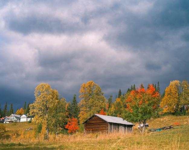 Vista panorâmica de uma velha casa de madeira com árvores de outono