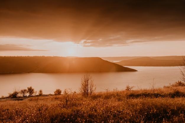 Vista panorâmica desde a falésia até ao grande rio, lago, mar à distância, silhuetas das ilhas, pôr do sol laranja ardente
