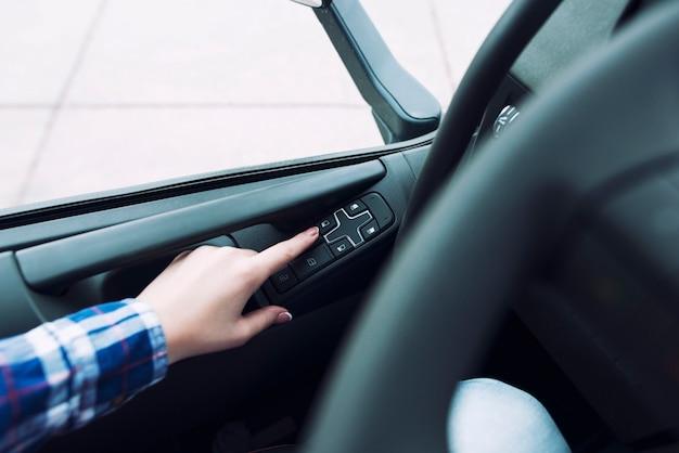 Vista panorâmica do controle do veículo com janelas e as mãos do motorista pressionando o botão para abrir a janela do veículo