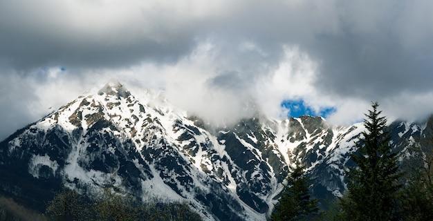 Vista panorâmica do cume das montanhas nevadas nas nuvens