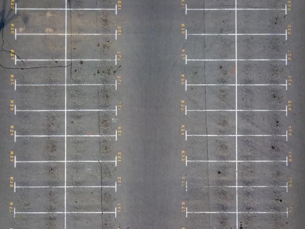 Vista panorâmica do drone acima do estacionamento vazio com linhas de marcação brancas no asfalto com lugares numerados. fundo de carros de estacionamento.