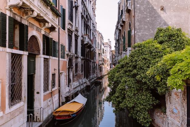 Vista panorâmica do estreito canal de veneza com edifícios históricos e barco da ponte. paisagem de dia ensolarado de verão