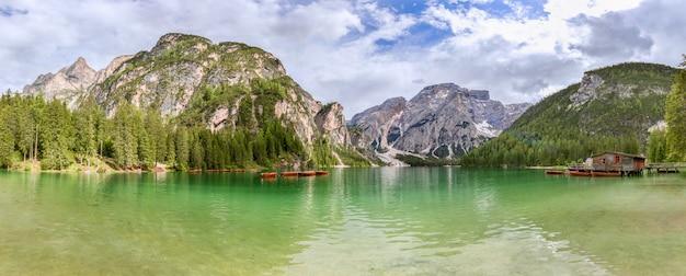Vista panorâmica do famoso lago alpino braies com uma casa-barco e barcos na superfície esmeralda do lago