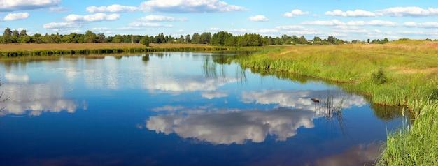Vista panorâmica do lago apressado de verão com reflexos de nuvens. imagem composta de seis tiros.