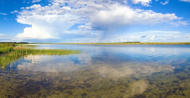 Vista panorâmica do lago de verão com reflexos de nuvens