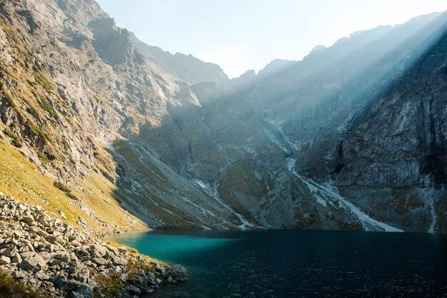 Vista panorâmica do lago morskie oko com água verde, montanhas rochosas e sol matinal