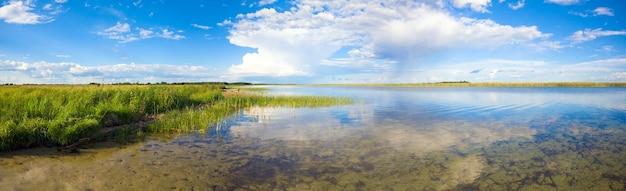 Vista panorâmica do lago verão com reflexos de nuvens. três tiros costuram a imagem.