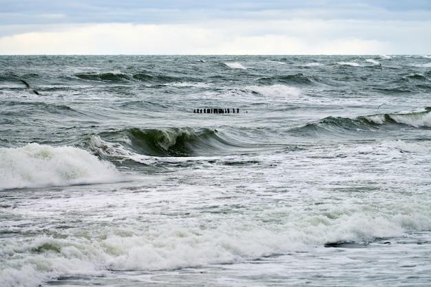 Vista panorâmica do mar azul com ondas borbulhantes e espumantes. quebra-mares de madeira longos vintage estendendo-se até o mar, a paisagem do mar báltico de inverno. silêncio, solidão, calma e paz.