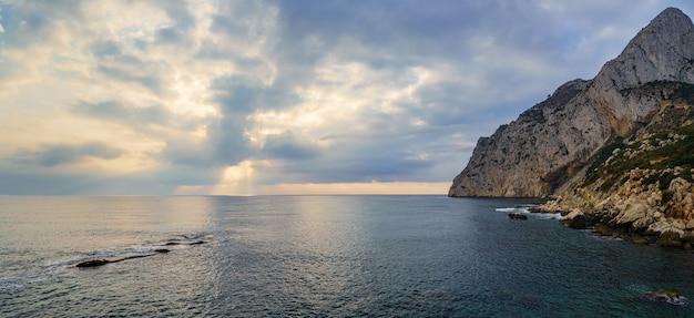 Vista panorâmica do mar com grande montanha à beira-mar e o pôr do sol dourado.