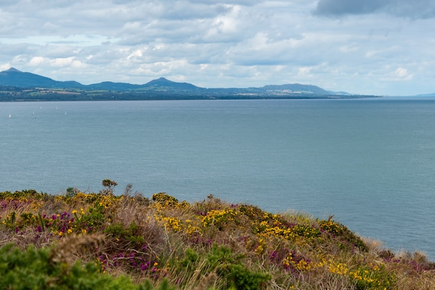 Vista panorâmica do mar da irlanda do farol principal de wicklow com montanhas de wicklow à distância.