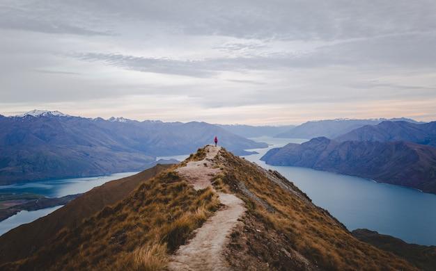Vista panorâmica do pico roys na nova zelândia, com montanhas baixas à distância sob a paisagem de nuvens