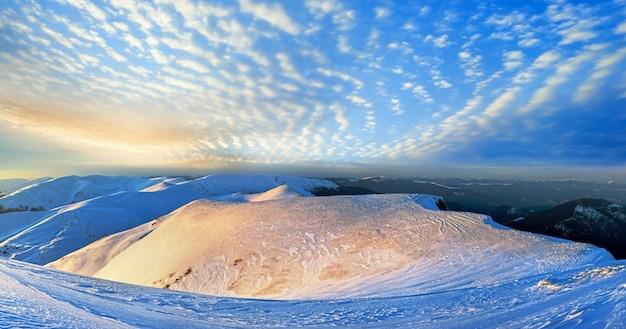Vista panorâmica do pôr do sol do cume da montanha em tons pastel dourados dos raios de sol da última noite (ucrânia, mt dos cárpatos, estação de esqui drahobrat). dez tiros costuram a imagem.