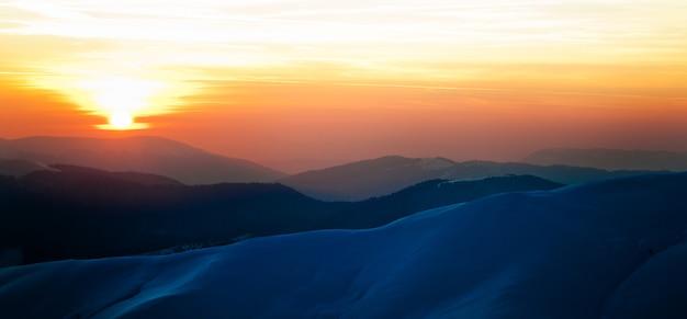 Vista panorâmica do pôr do sol nas colinas de inverno cobertas de neve e o sol se pondo acima