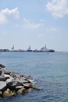Vista panorâmica do porto. costa com grandes pedras e superfície de mar calma. verão.