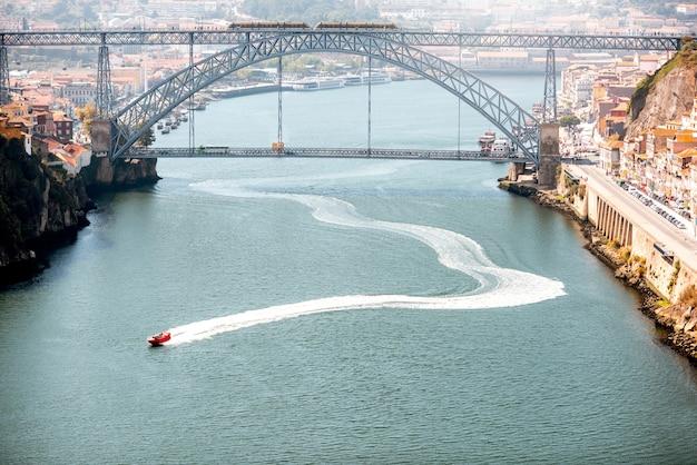 Vista panorâmica do rio douro com flutuadores de lancha e uma bela ponte de ferro na cidade do porto, portugal