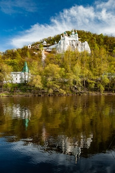 Vista panorâmica do templo e do mosteiro ortodoxo em uma colina coberta de árvores decíduas