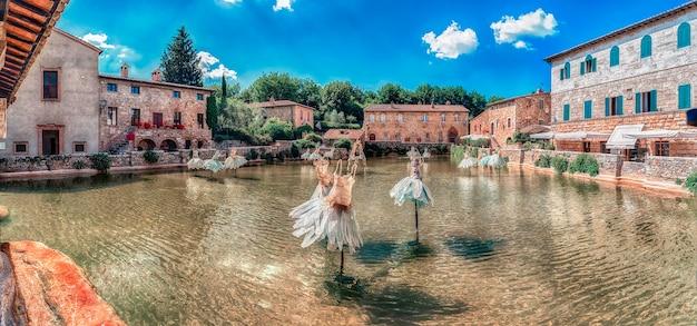 Vista panorâmica dos icônicos banhos termais medievais, importante marco e pontos turísticos na cidade de bagno vignoni, província de siena, toscana, itália