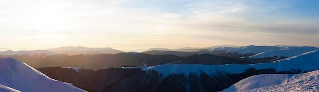 Vista panorâmica dos picos das montanhas de inverno cobertos de neve em dia claro ou ao anoitecer no inverno. conceito de paisagem do país das maravilhas do inverno