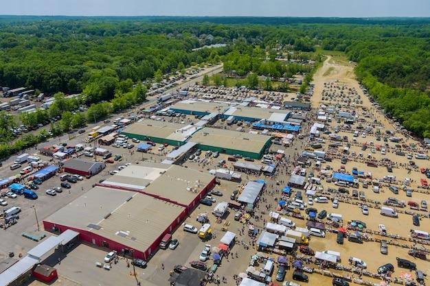 Vista panorâmica na cobertura do mercado de pulgas com diversos itens e multidões de compradores