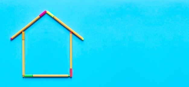 Vista panorâmica superior de canetas fluorescentes formando o desenho de uma casa em fundo azul pastel.
